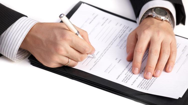 Mann füllt Formular zur Firmengründung aus